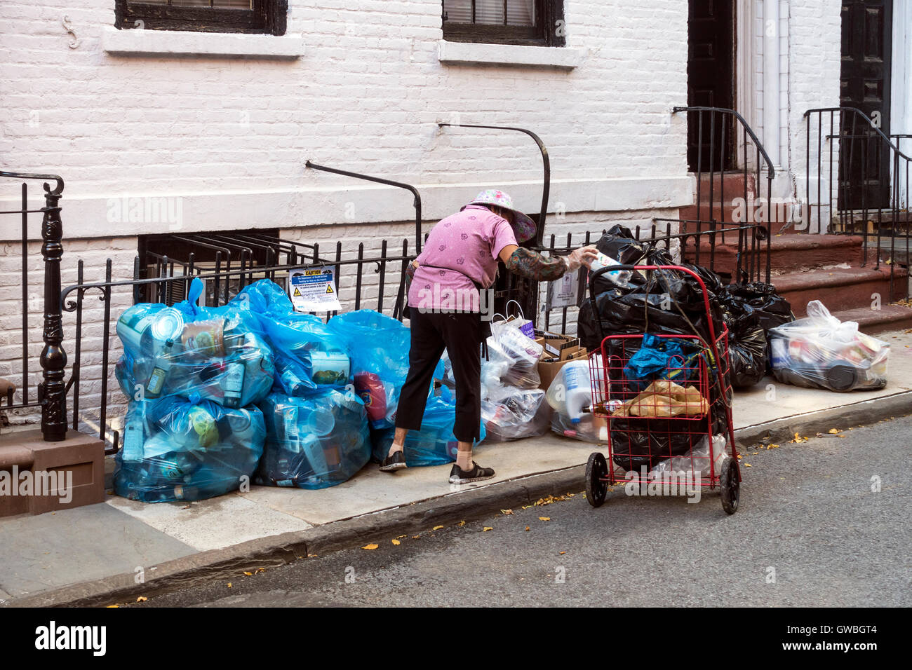 Older Asian woman picks bottles and cans from trash in order to collect deposits - Stock Image
