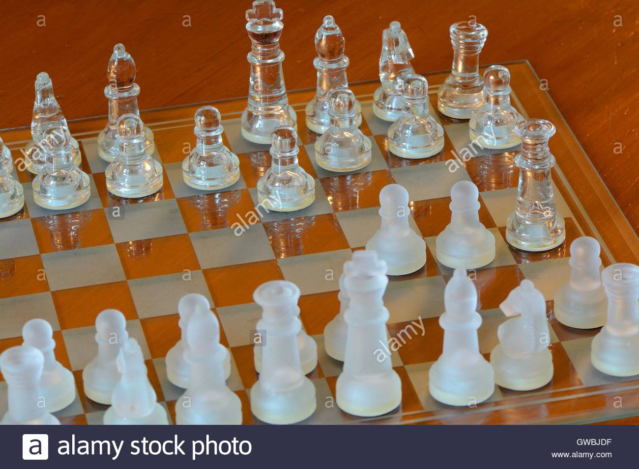 glass chess board set with pieces at fools checkmate stock photo