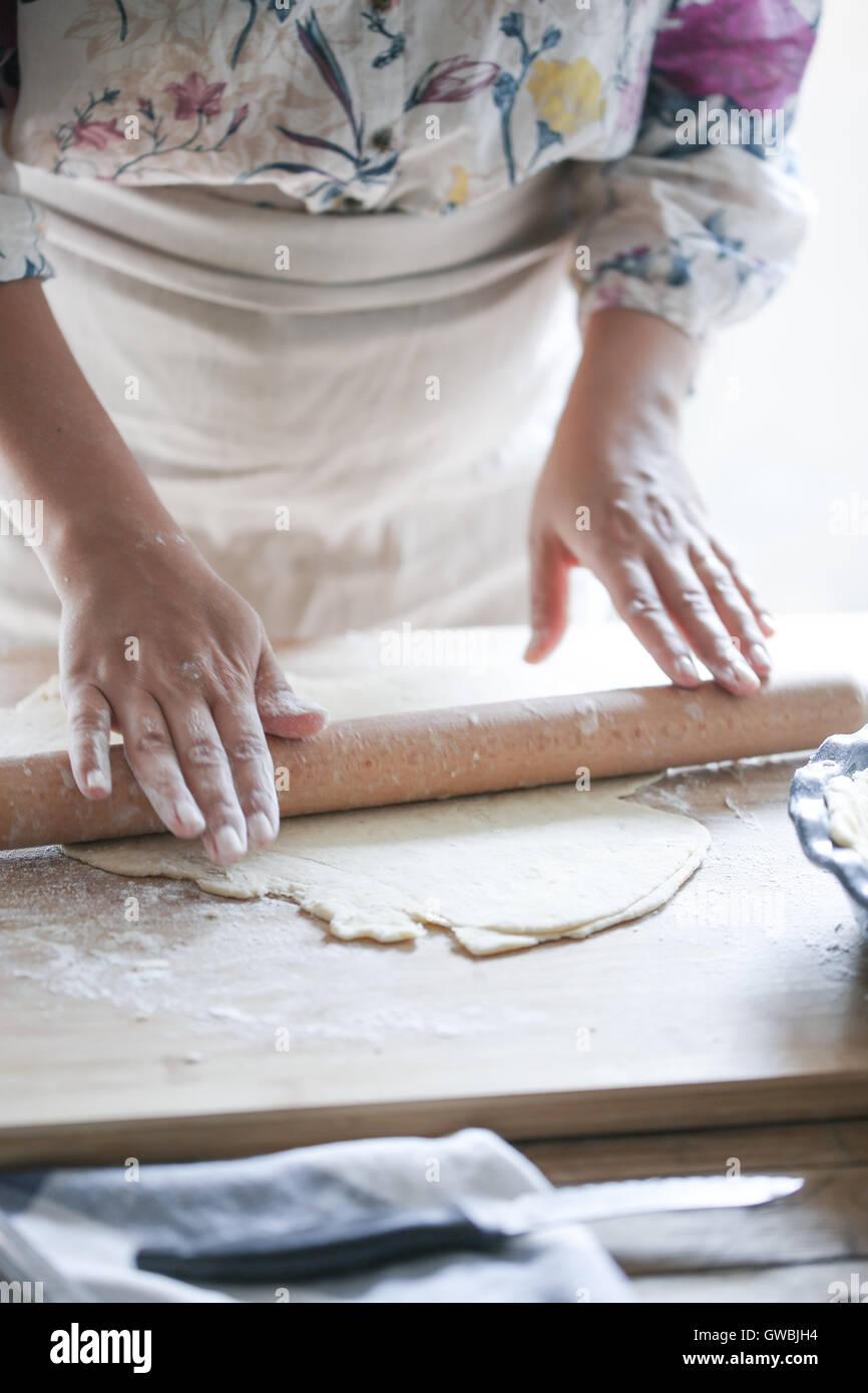 Woman rolling dough - Stock Image
