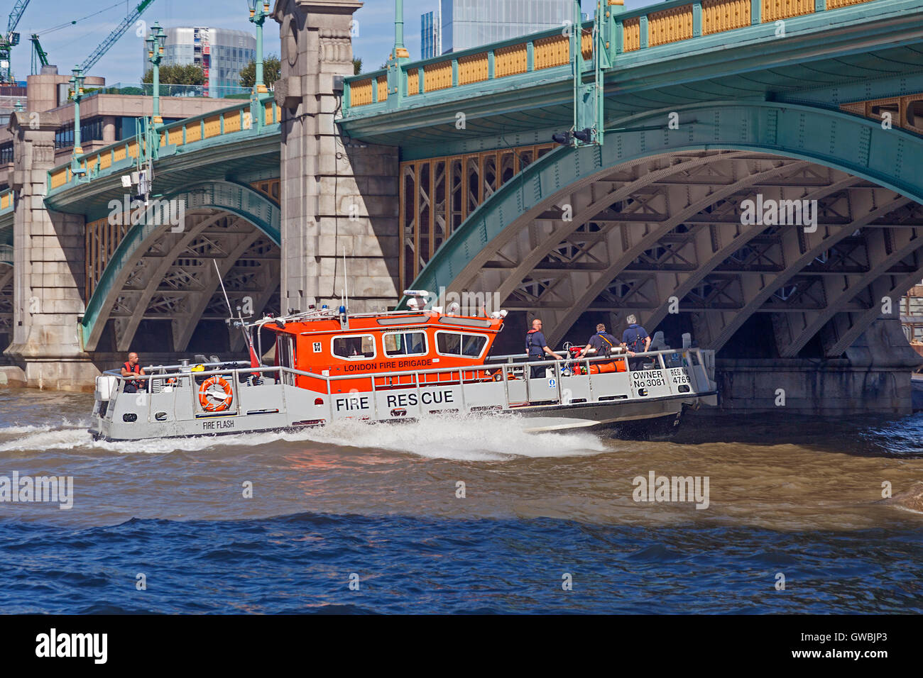 A Fire Rescue vessel of the London Fire Brigade speeding downstream under Southwark Bridge - Stock Image