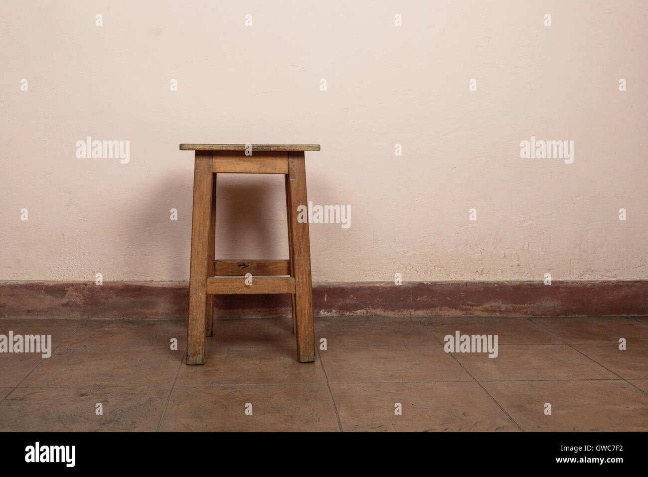 Rustic wooden stool, pink wall background - Stock Image