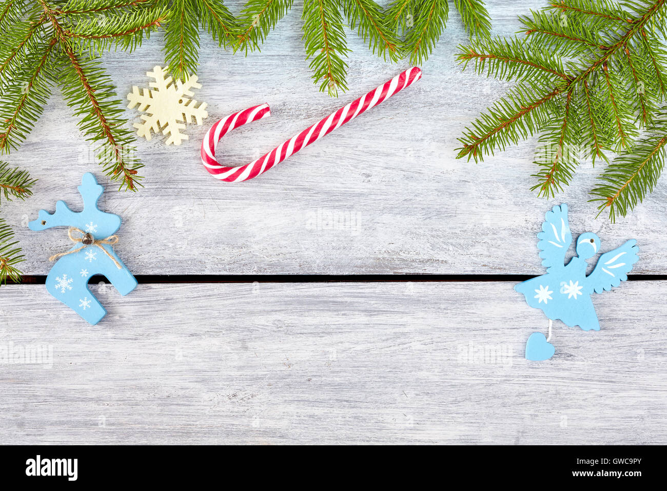 Christmas background, spruce branches with decorations on a rustic wooden table, top view with copy space. - Stock Image