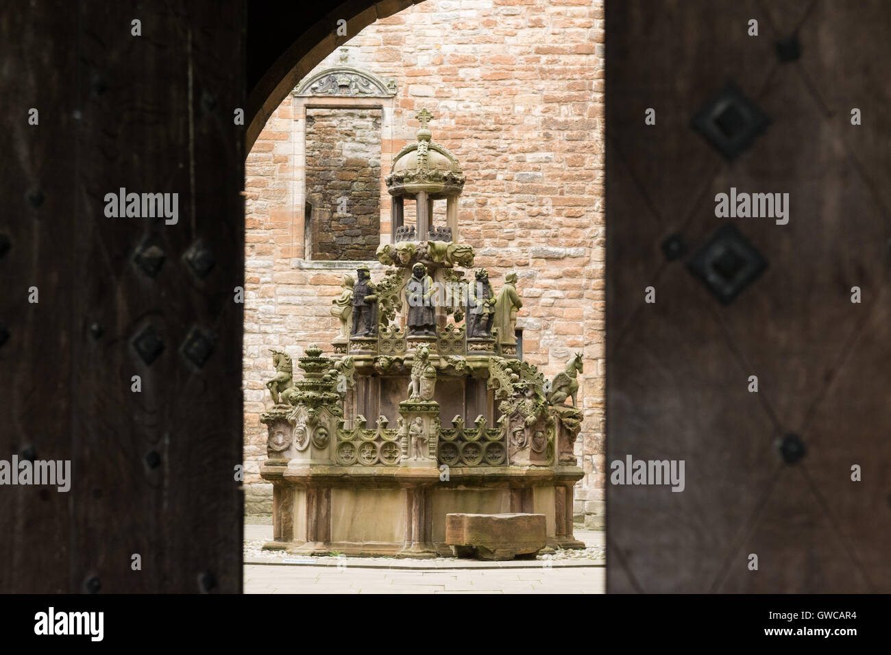 Linlithgow Palace James V restored fountain in the centre of the courtyard seen through the doors of the former Stock Photo