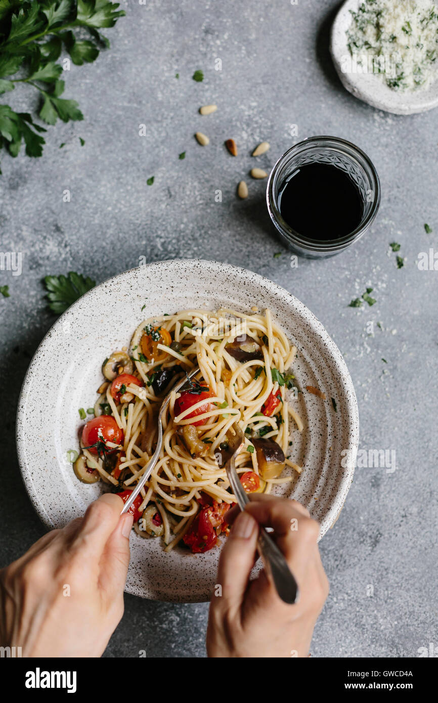 A woman's hands are photographed as she is rolling spaghetti. - Stock Image