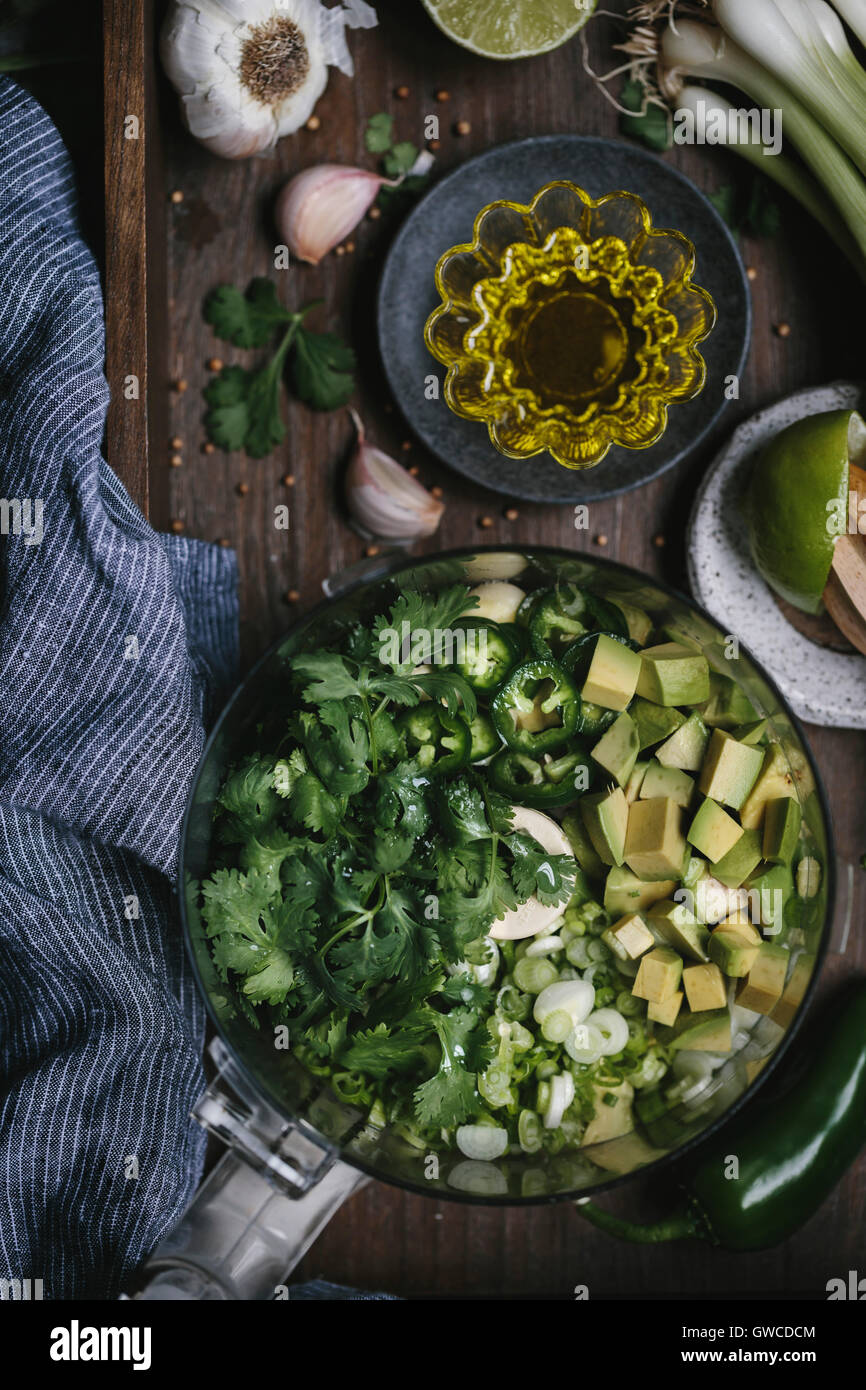 Ingredients for Creamy Avocado Salad Dressing are placed in a food processor and photographed from the top view. - Stock Image