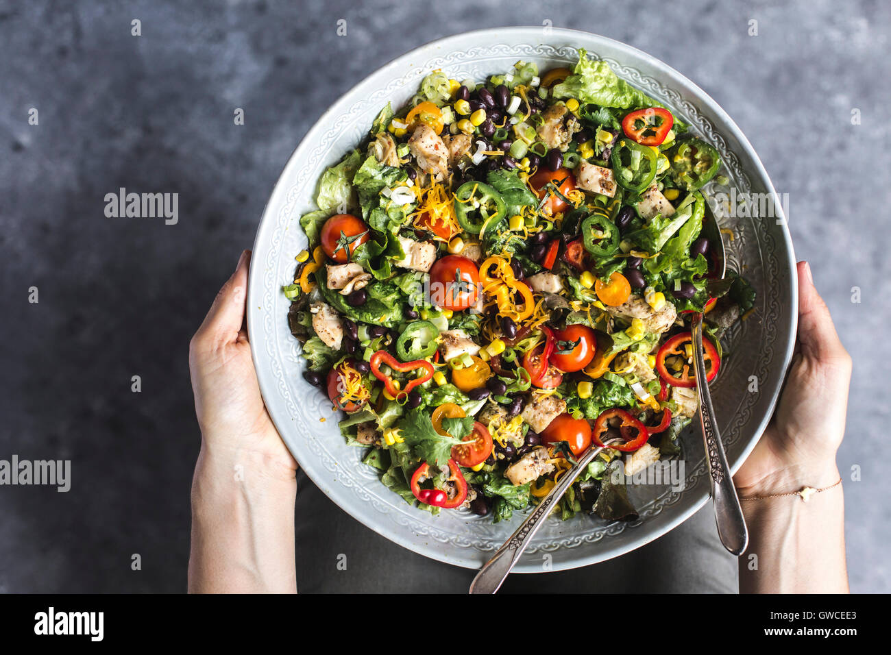 A large bowl of Southwestern Chicken Salad with Creamy Avocado Dressing in a woman's hands is photographed from - Stock Image