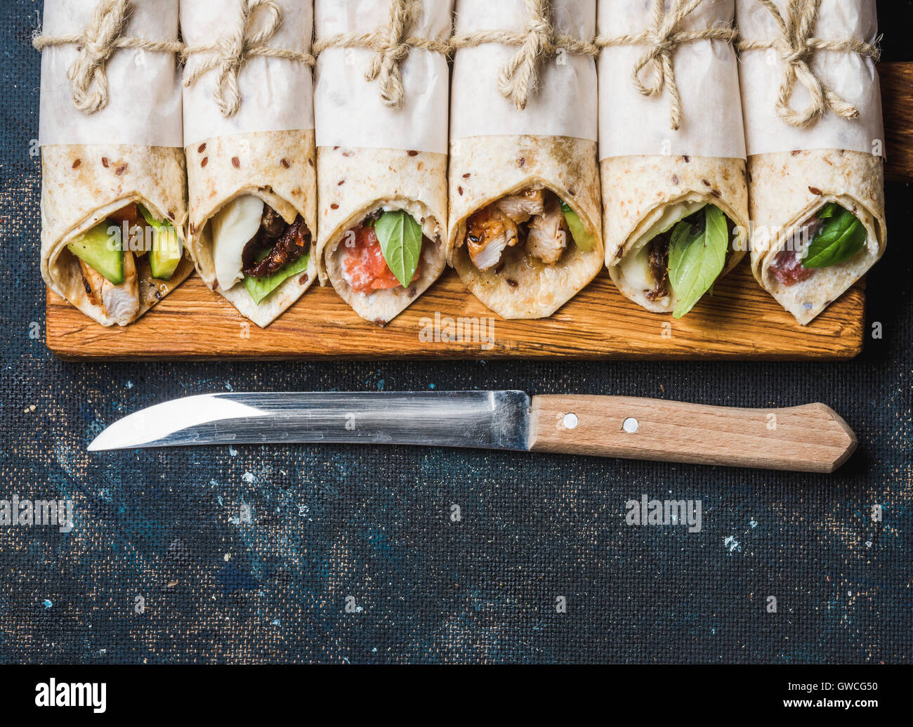Tortilla wraps with various fillings on rustic wooden board and knife over dark blue painted plywood background, - Stock Image