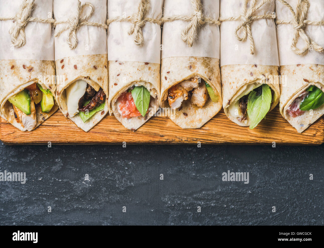Tortilla wraps with various fillings on wooden board over dark grey grunge concrete background, top view, copy space, - Stock Image