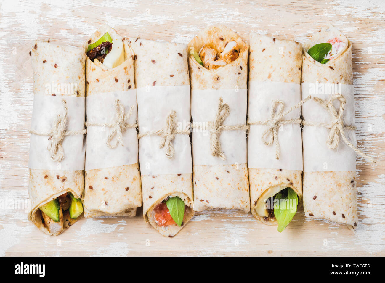 Tortilla wraps with various fillings on shabby white painted wooden background, top view, horizontal composition. - Stock Image