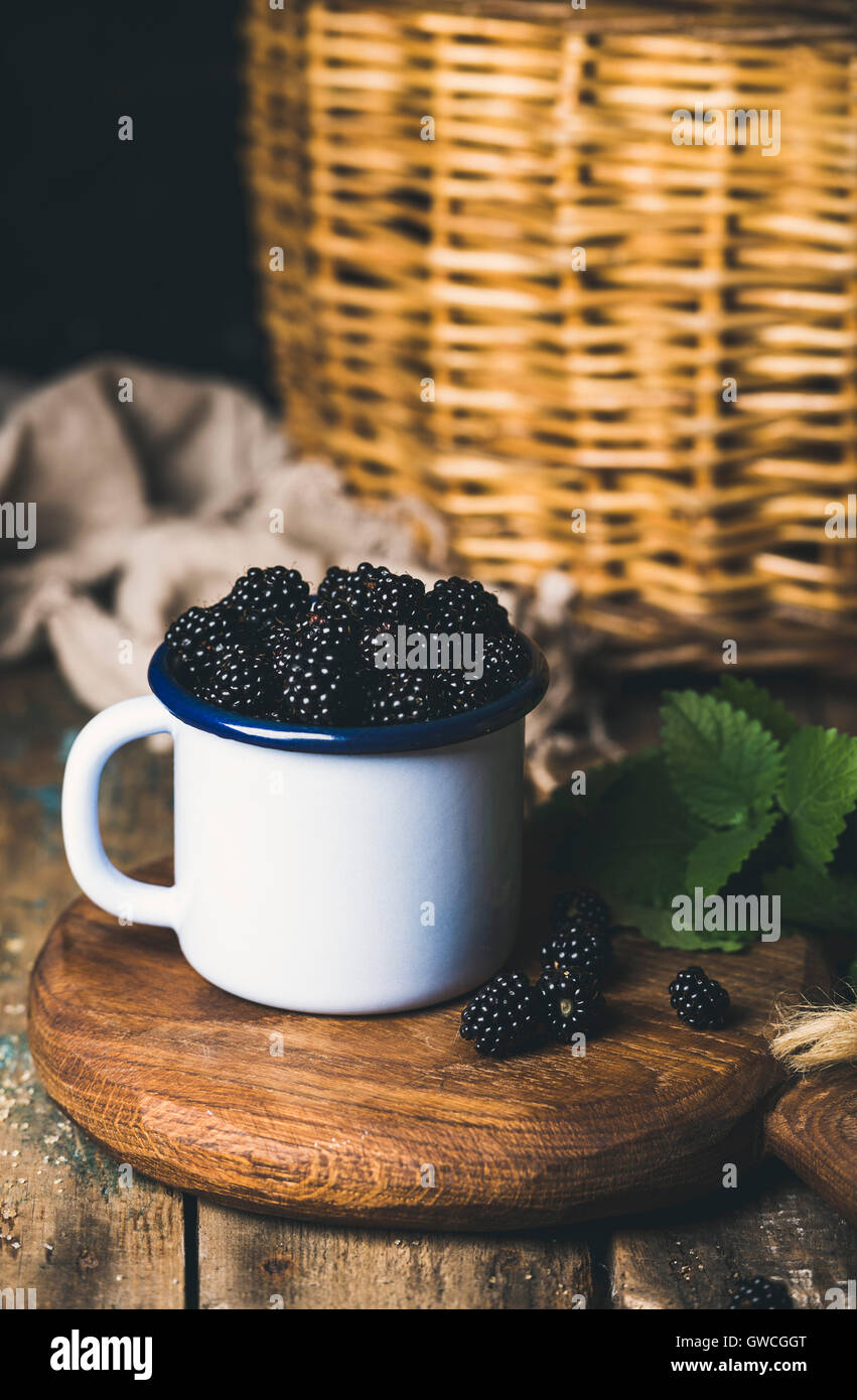 Fresh Blackberries in white cup on round serving wooden board over rustic background, selective focus, vertical - Stock Image