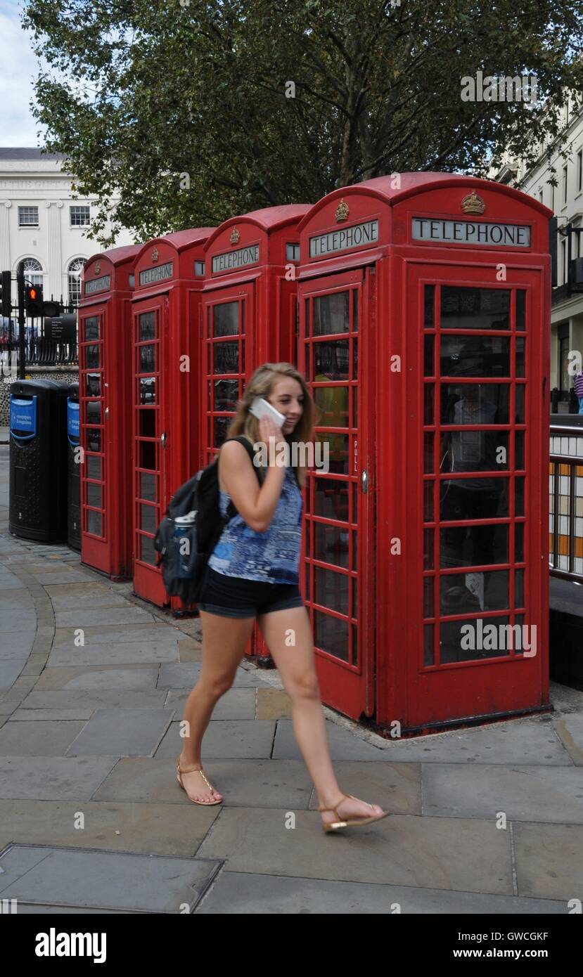 A young woman talking on her mobile phone, walks past a row of phone boxes. - Stock Image