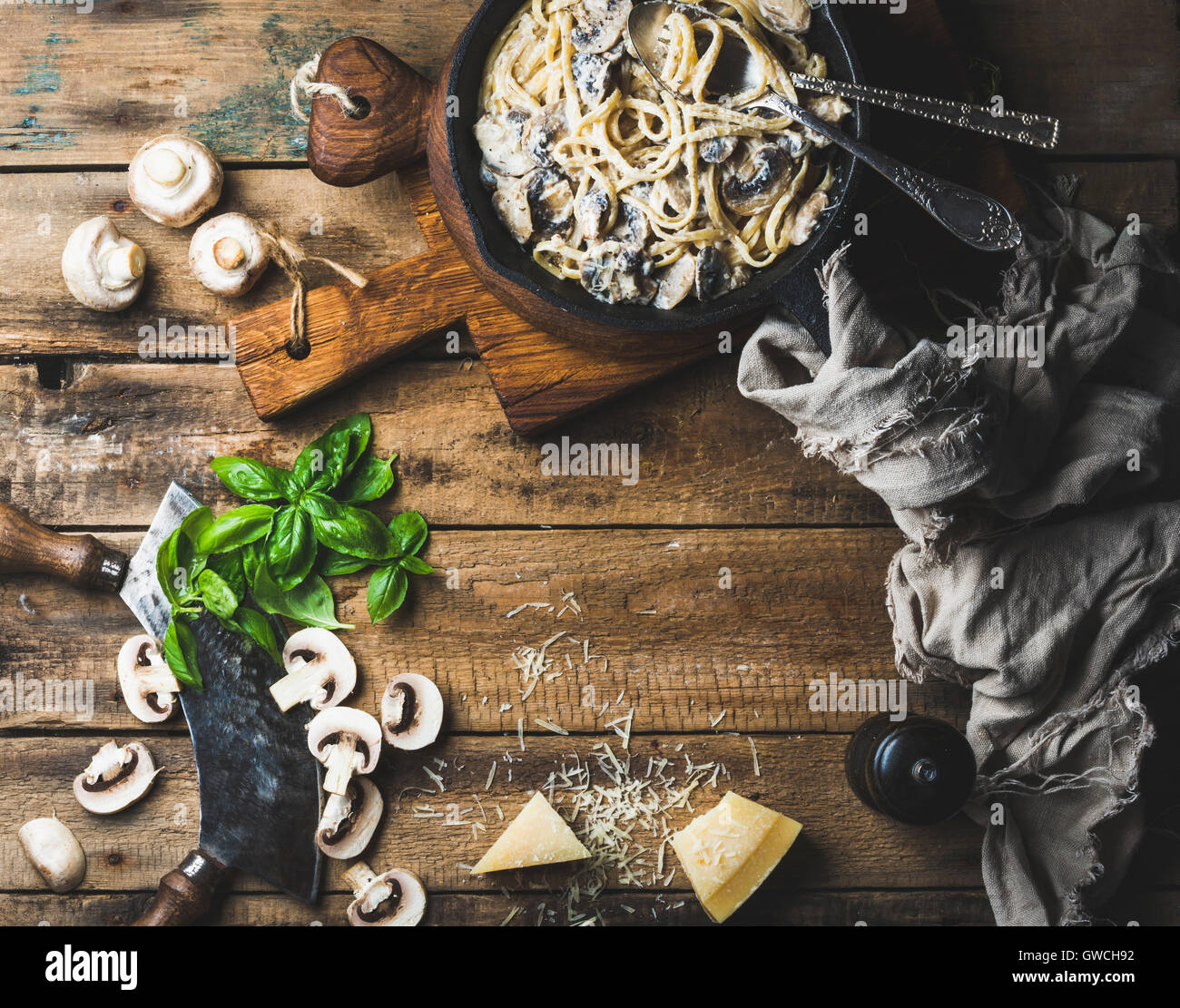 Italian style dinner with copy space. Creamy mushroom pasta spaghetti in cast iron pan with Parmesan cheese, fresh - Stock Image