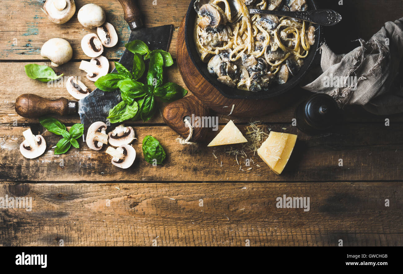Italian style dinner. Creamy mushroom pasta spaghetti in cast iron pan with Parmesan cheese, fresh basil and pepper - Stock Image