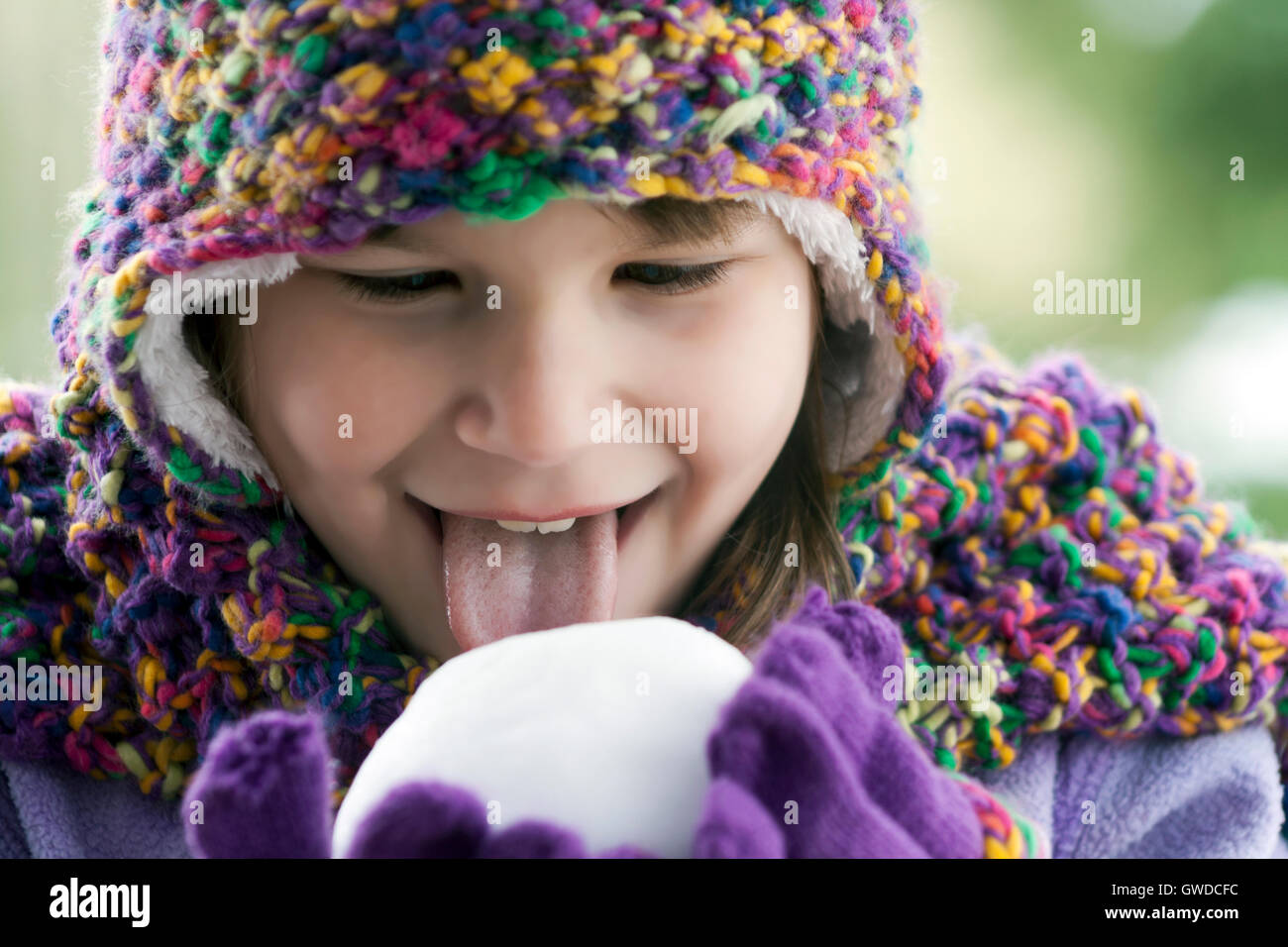 Young girl licking a snowball. - Stock Image
