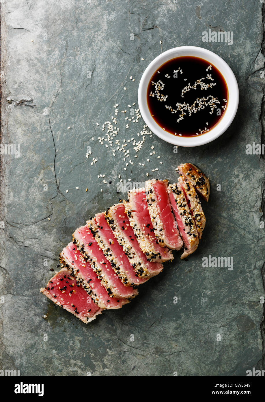 Sliced grilled Tuna steak in sesame and soy sauce on stone slate board - Stock Image