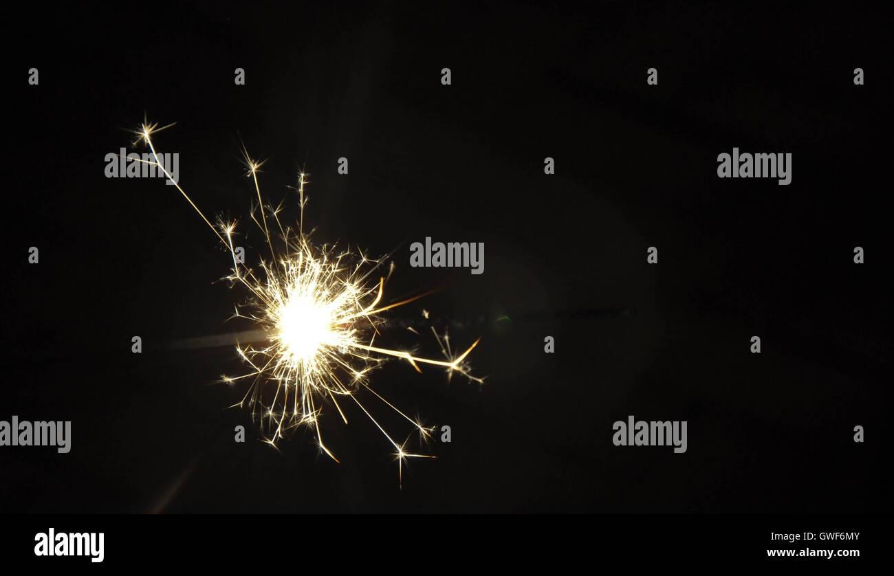 Closeup of handheld sparkler firework illuminated with a dark night background. - Stock Image