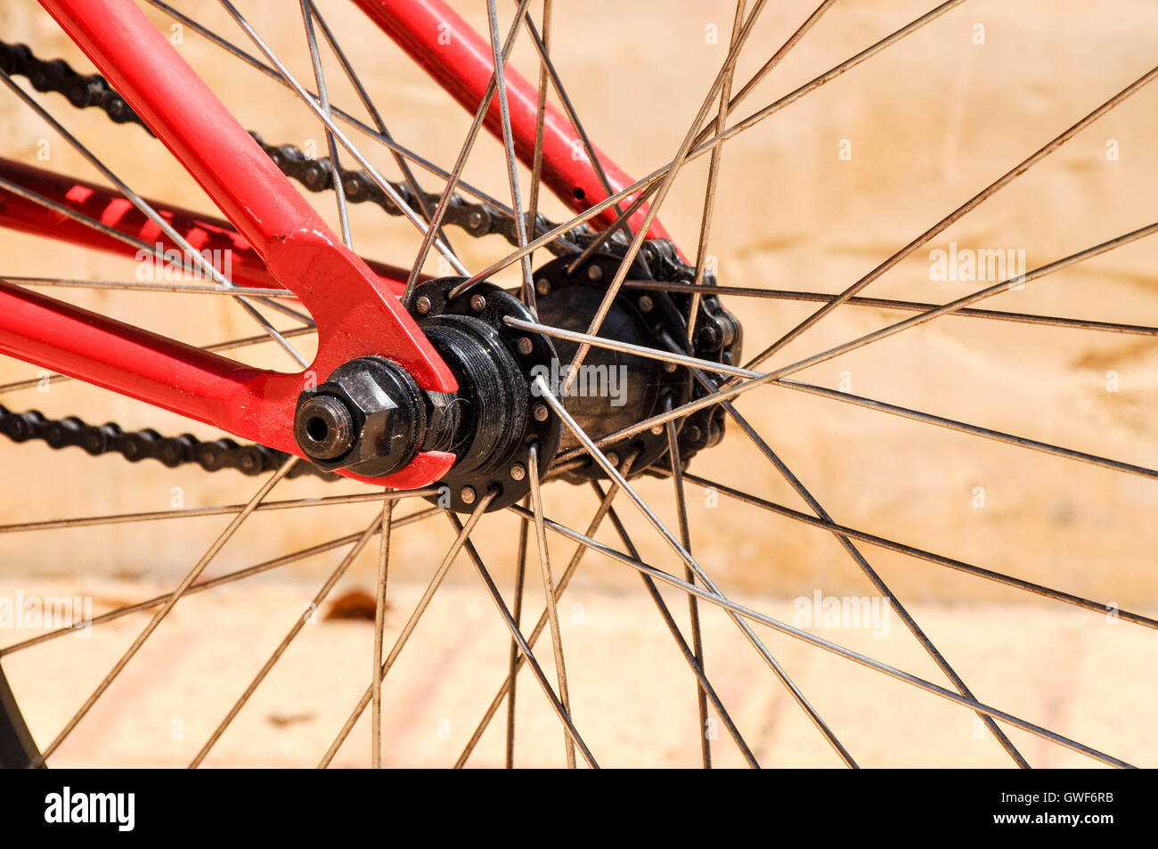 Abstract closeup of the red metal of bicycle frame with radiating spokes with a blurred background in outdoor setting. - Stock Image