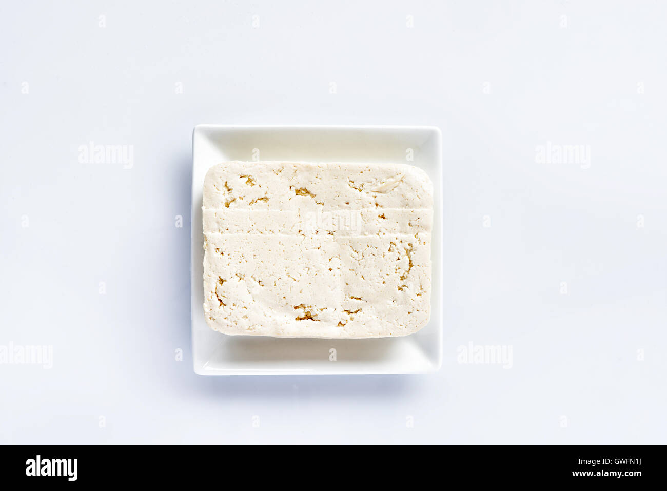 Tofu on a white plate on a white table, fresh vegetarian food, meat substitute - Stock Image