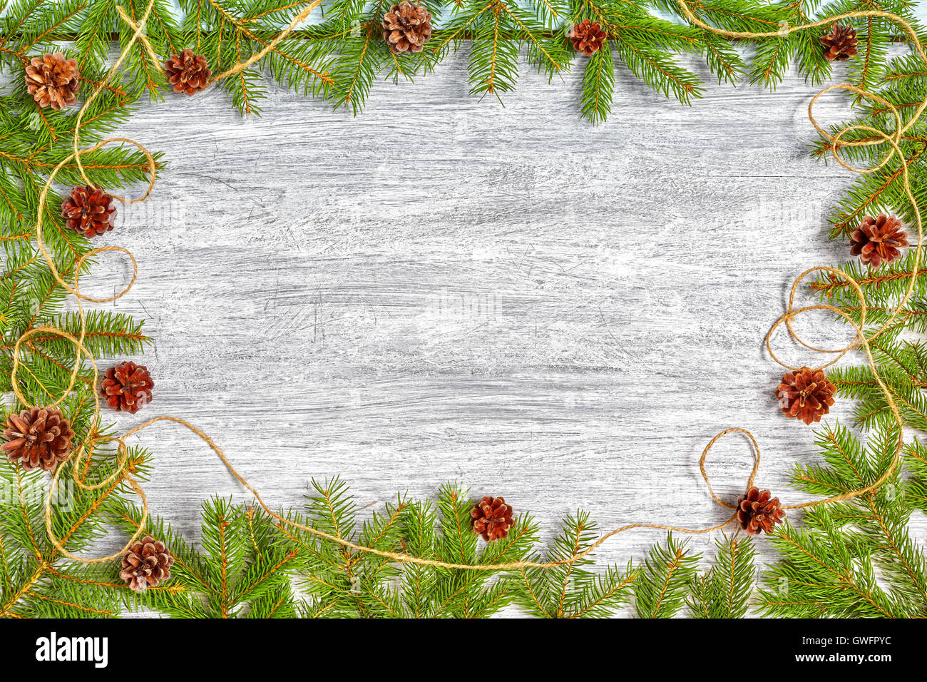Christmas background, spruce branches frame with pine cones on a rustic wooden table, top view with copy space. - Stock Image