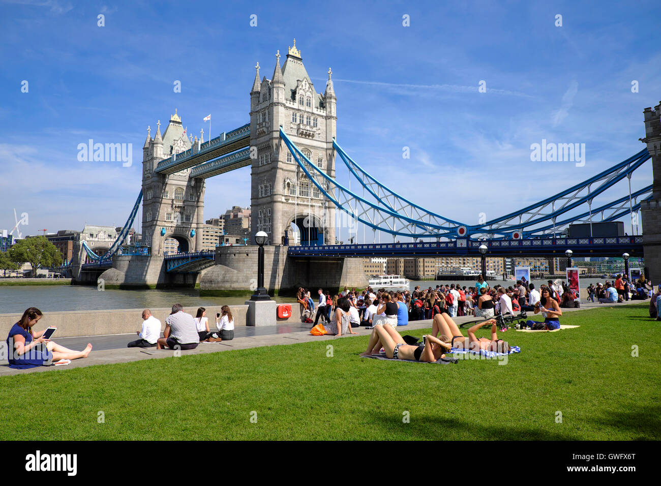 London, UK. 13th September, 2016. UK Weather:  Sun bathers make the most of the Indian summer at Tower Bridge, London - Stock Image