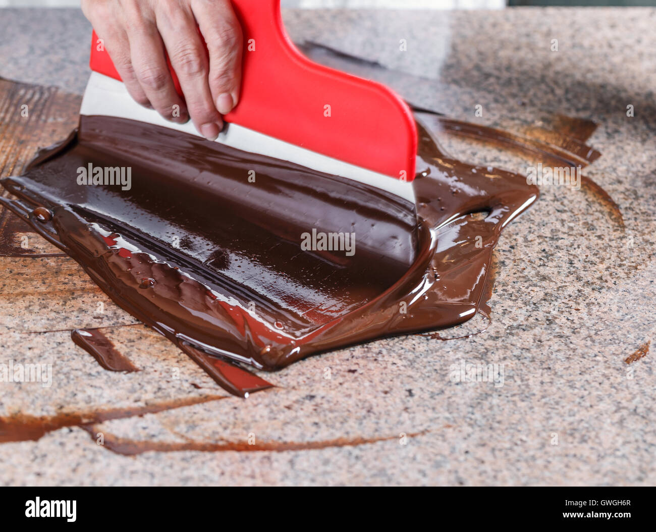 Tempering of the chocolate on the marble surface Stock Photo