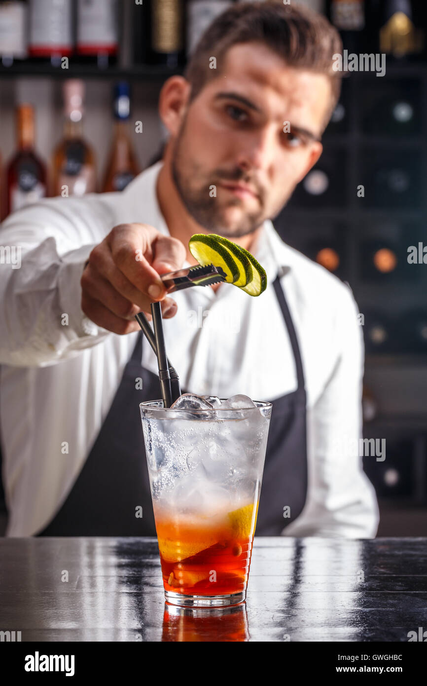 Barman decorating cocktail with lime - Stock Image