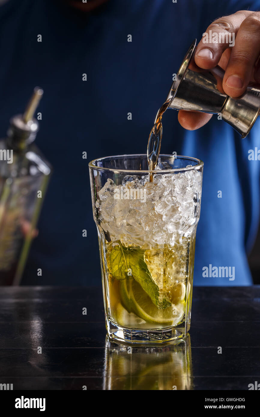 Bartender pouring strong alcoholic drink into glass - Stock Image