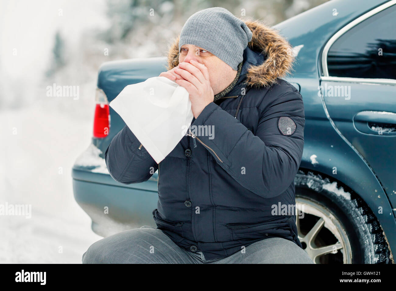 Stressful man breathe into paper bag near car on road - Stock Image