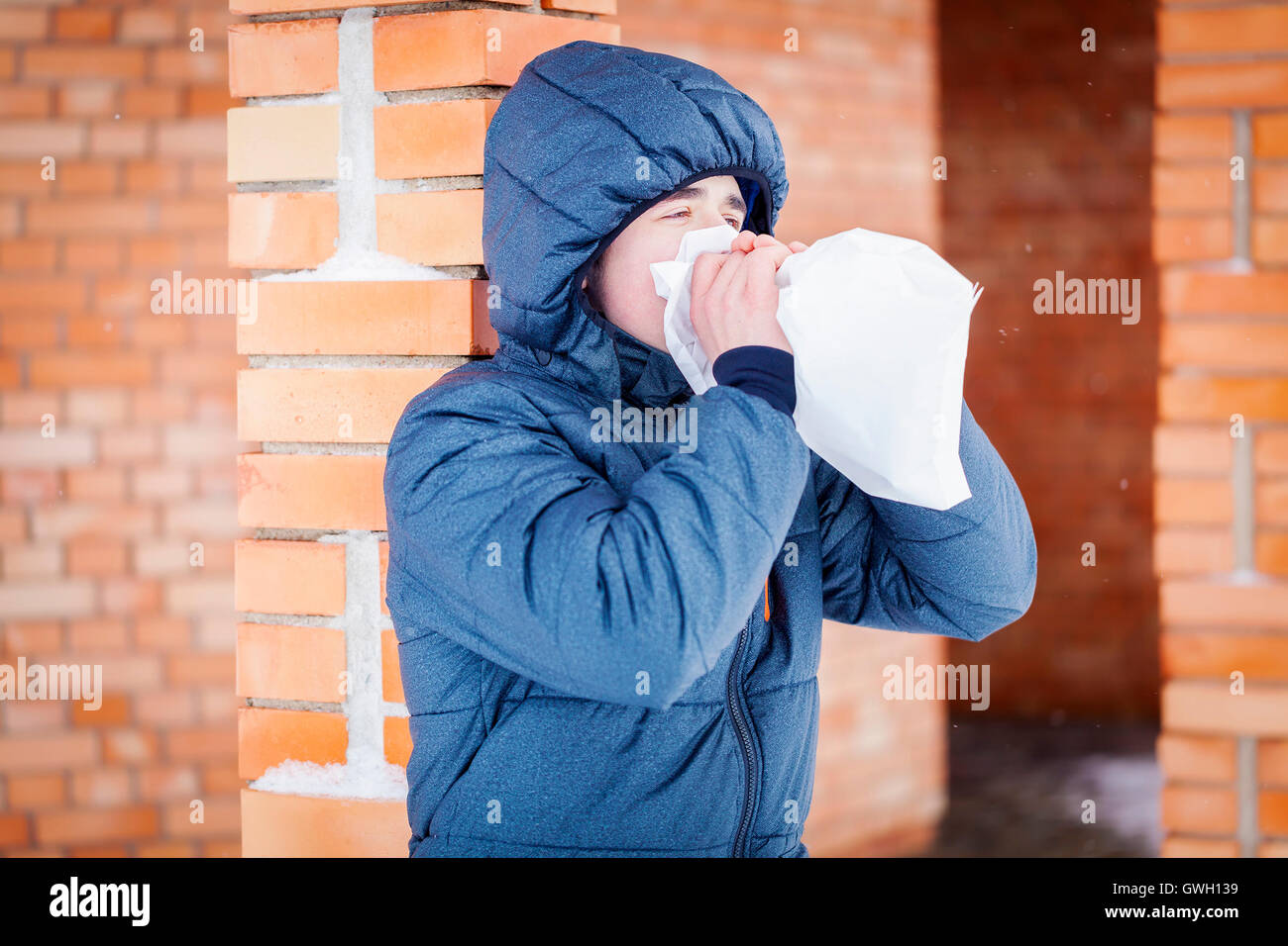 Stressful Teenager breathe into paper bag near building in winter - Stock Image