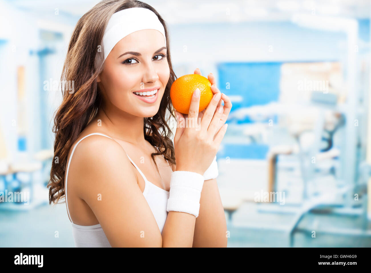 Portrait of happy smiling lovely woman with orange, at fitness center or gym - Stock Image