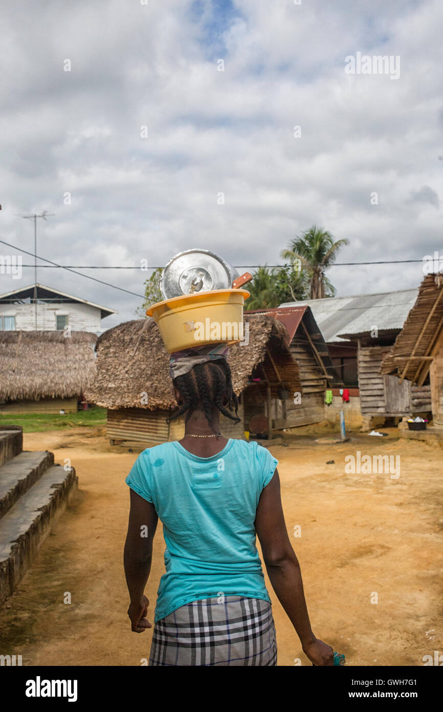 Maroon woman carrying bowl with dishes on her head in Suriname - Stock Image