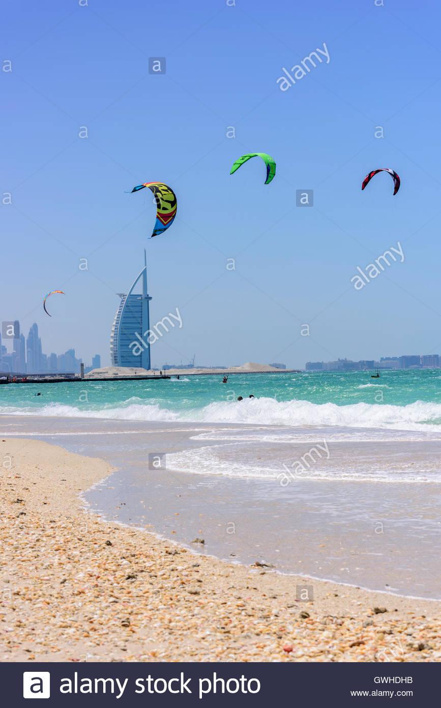man kite-surfing at Jumeirah Kite Beach with Burj Al Arab in background. Dubai, United Arab Emirates. - Stock Image