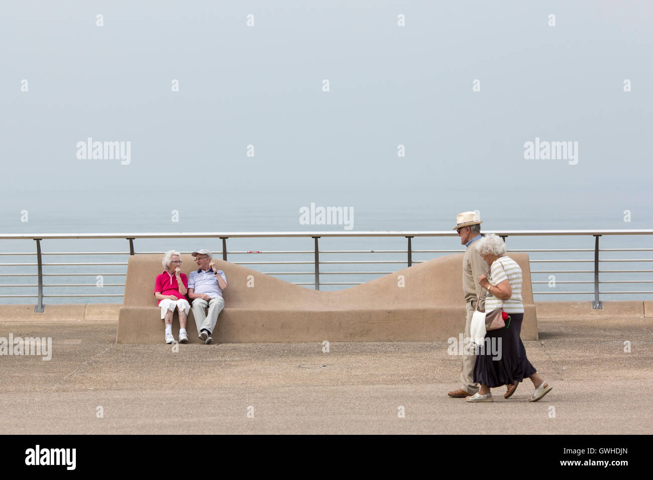 Two elderly couples enjoy warm weather on the promenade at  Blackpool , England - Stock Image