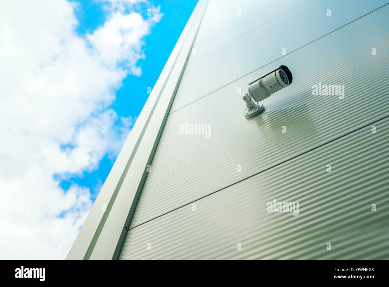Security surveillance camera on shopping mall exterior wall - Stock Image