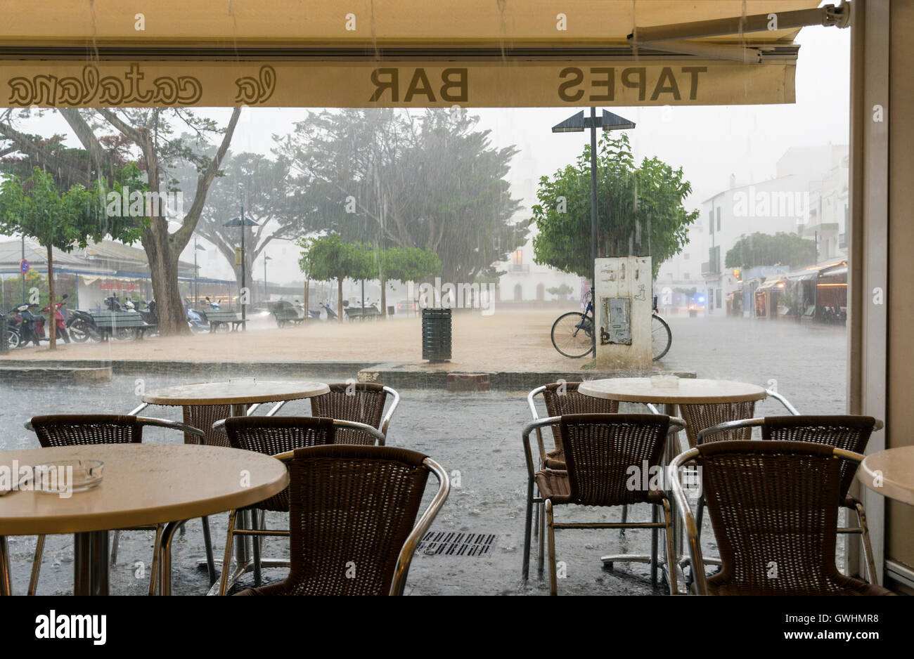 Heavy rainfall viewed through the open front of a bar on the Costa Brava, Spain - Stock Image