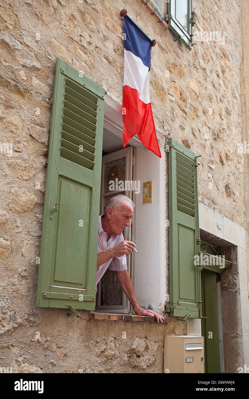 Elderly Frenchman smoking leaning out window - Stock Image