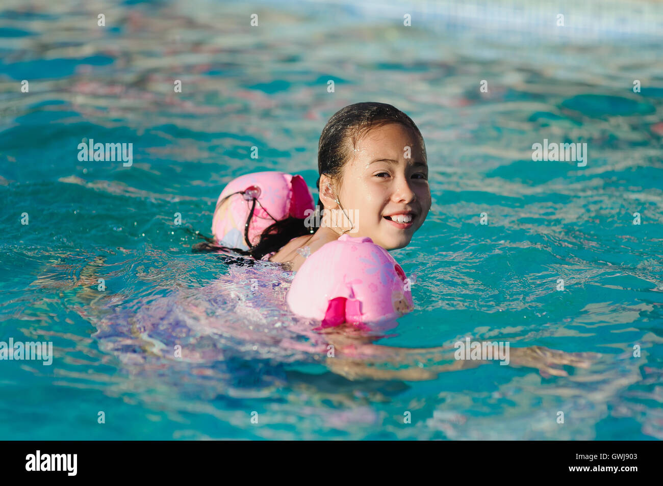 Swimming Pool Wings : Child with water wings in swimming pool stock photo