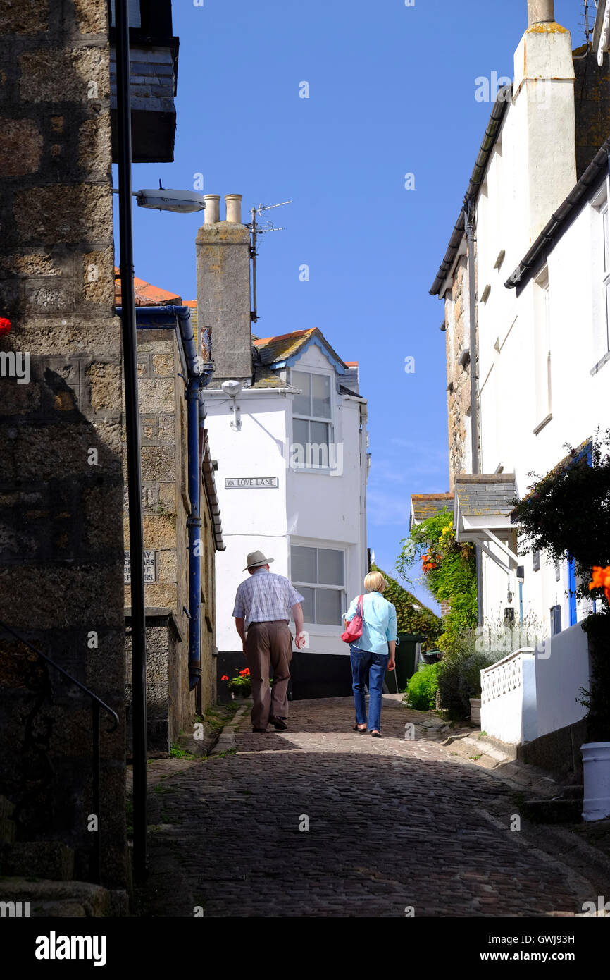 Couple walking along narrow street in St Ives - Stock Image