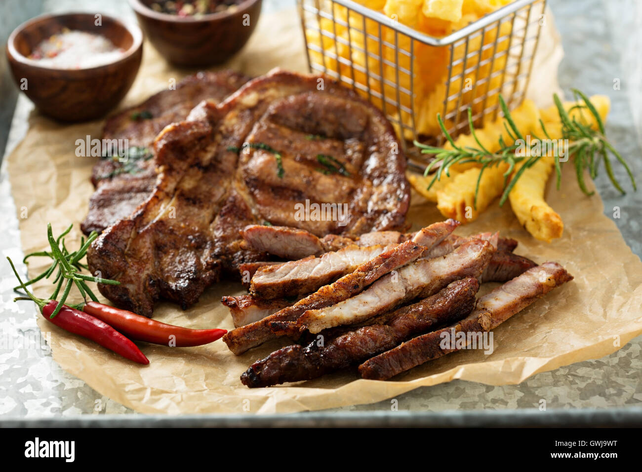 Grilled pork with french fries - Stock Image