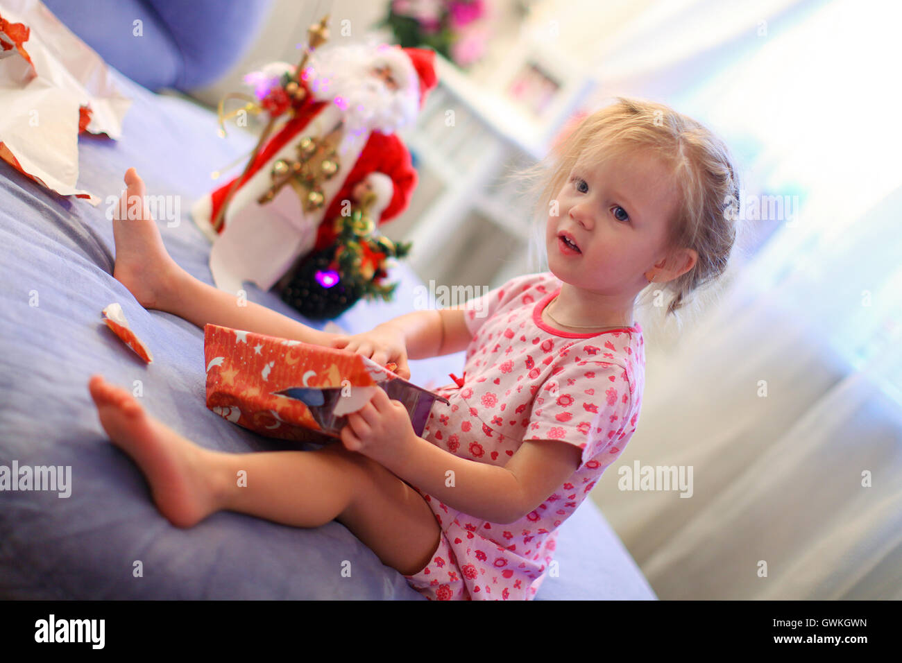 Little adorable girl early in the morning opening Christmas gifts ...