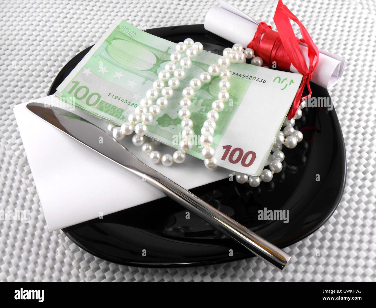 Money on plate, knife, diamonds and gift bow on white paper Stock Photo