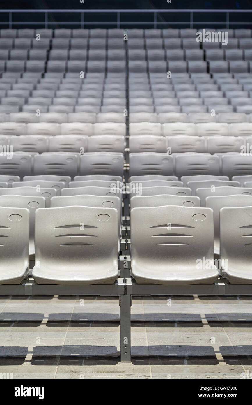 Many rows of empty plastic seats at a grandstand, viewed from the front. - Stock Image