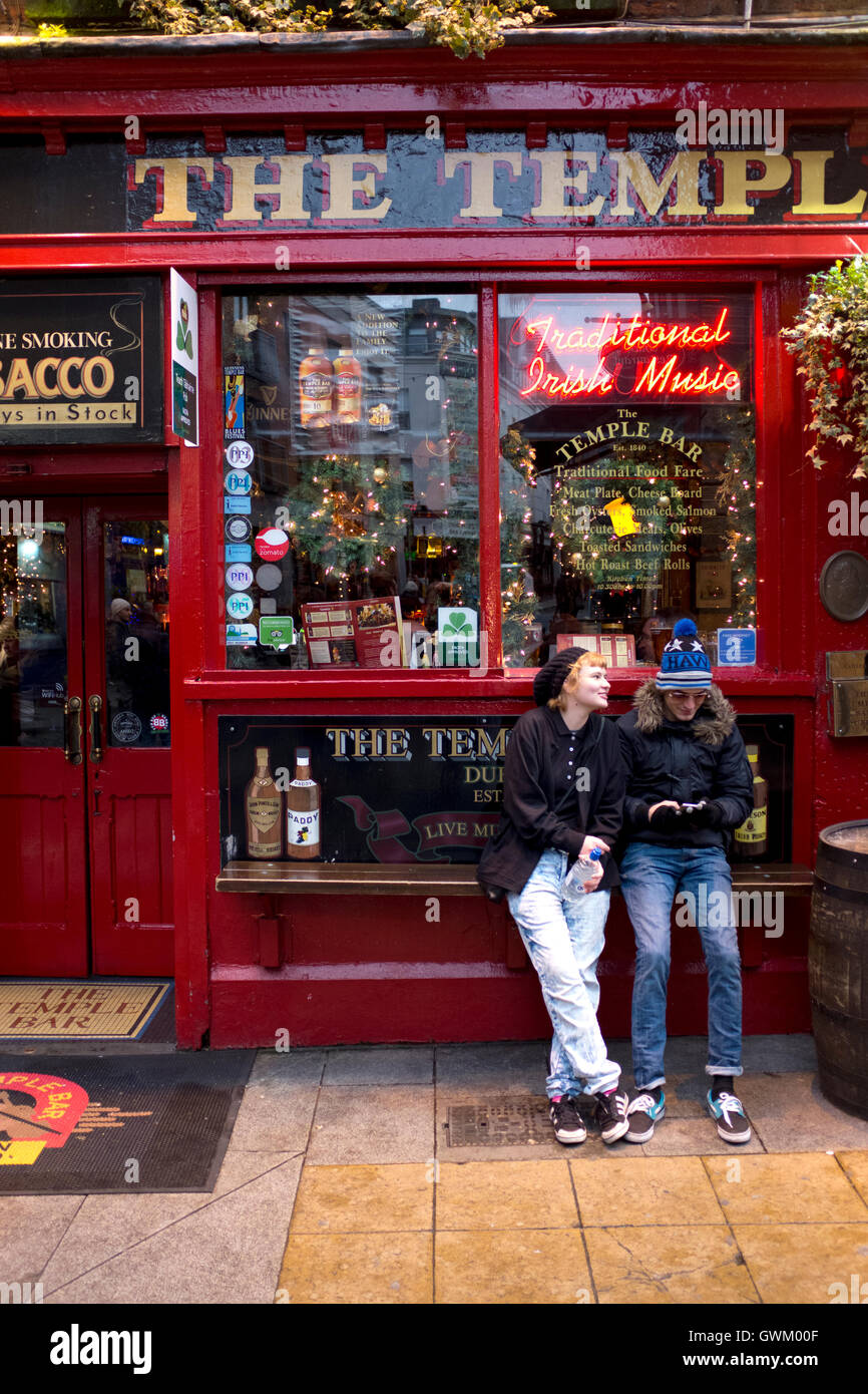 Two tourists sitting outside a pub in Temple Bar, Dublin, Ireland - Stock Image