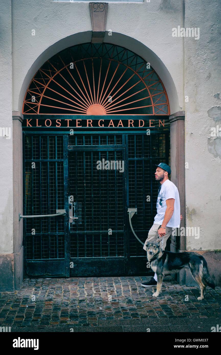 A man and his dog standing outside Klostergaarden condominium, Copenhagen, Denmark Stock Photo