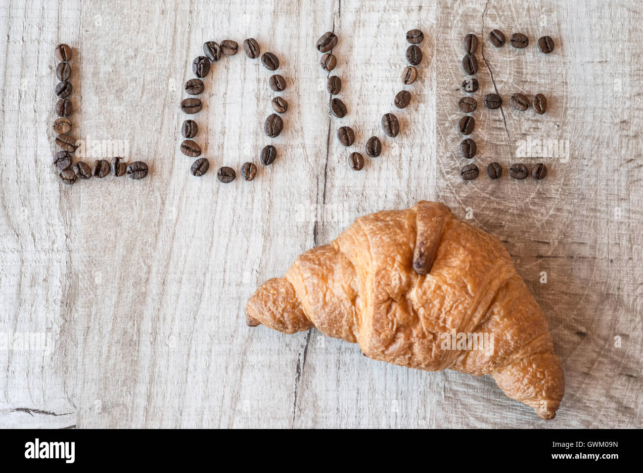 croissant on wooden background. title coffee beans love - Stock Image