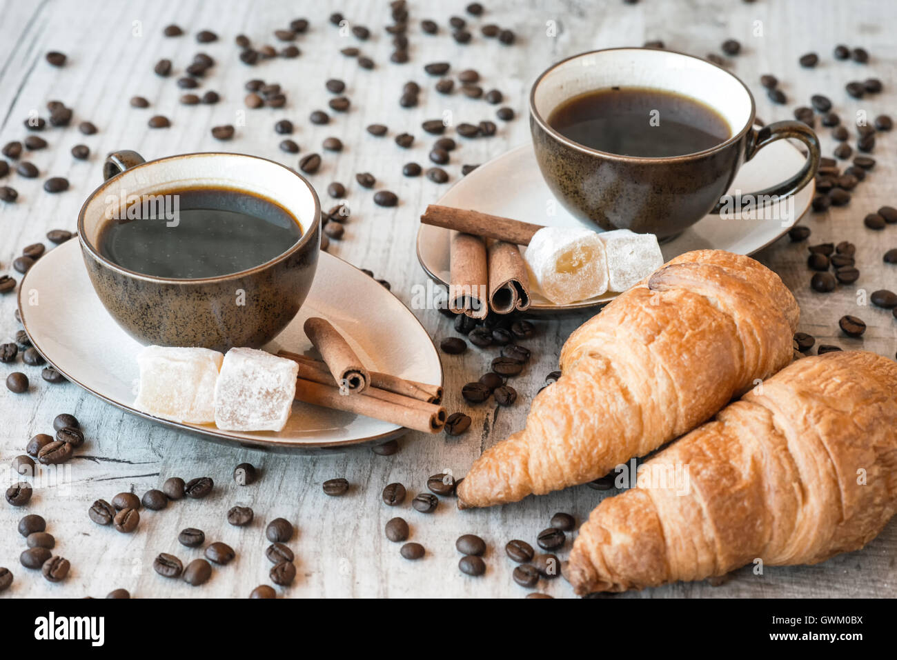 Cup of coffee with grains, croissant on wooden background - Stock Image