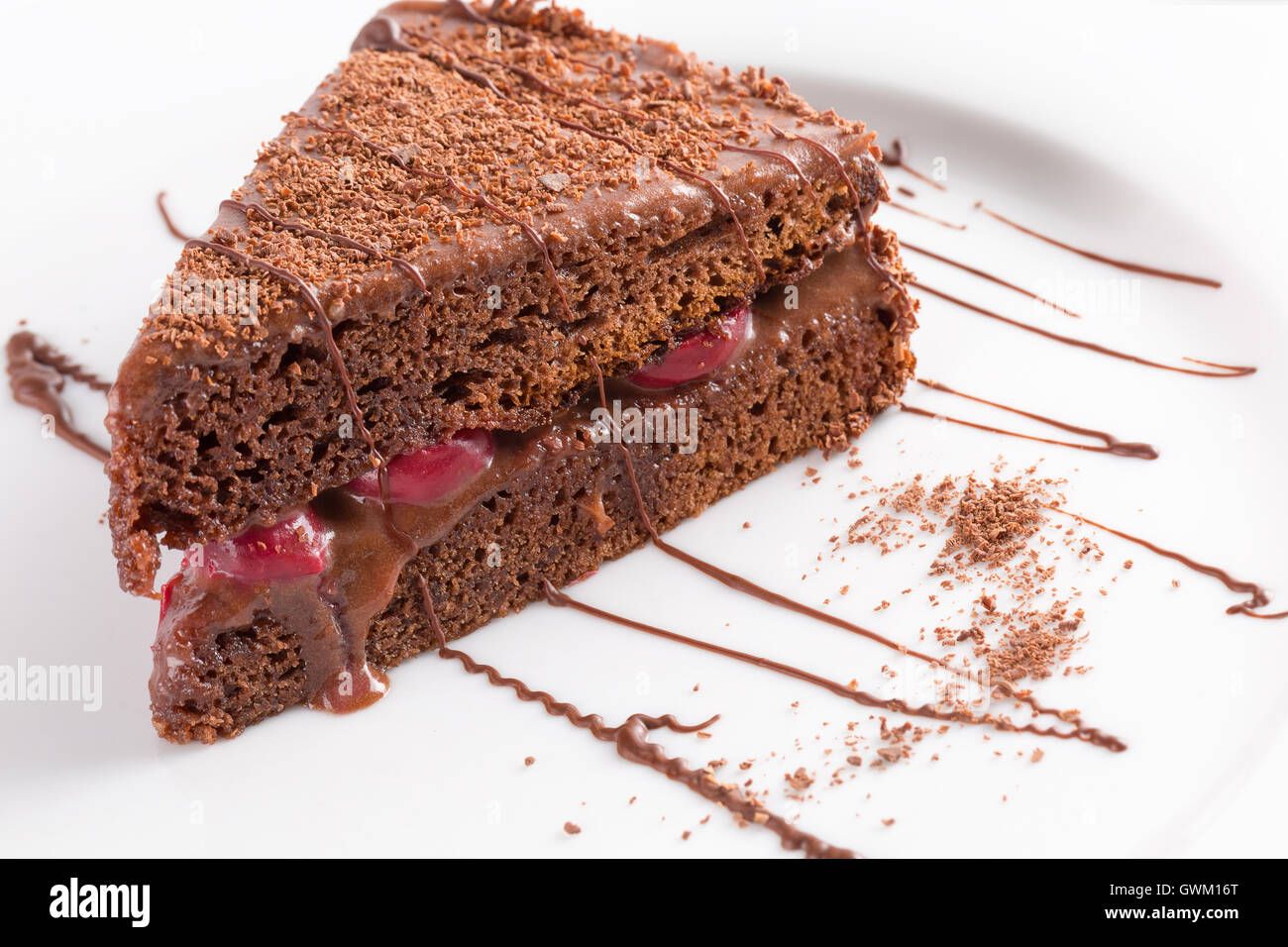 chocolate cheese cake with cherries on white plate. - Stock Image