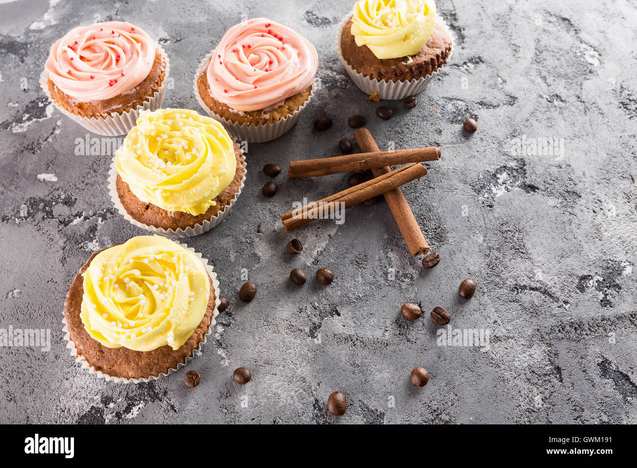 cupcakes with cream on grey stone background. - Stock Image