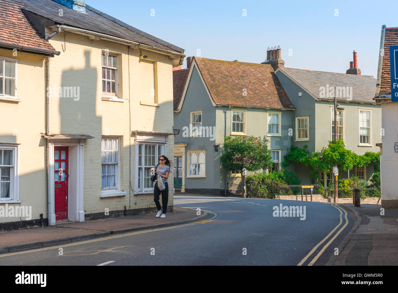 Suffolk village Clare, a young woman walks along Nethergate Street in the centre of the Suffolk village of Clare, - Stock Image