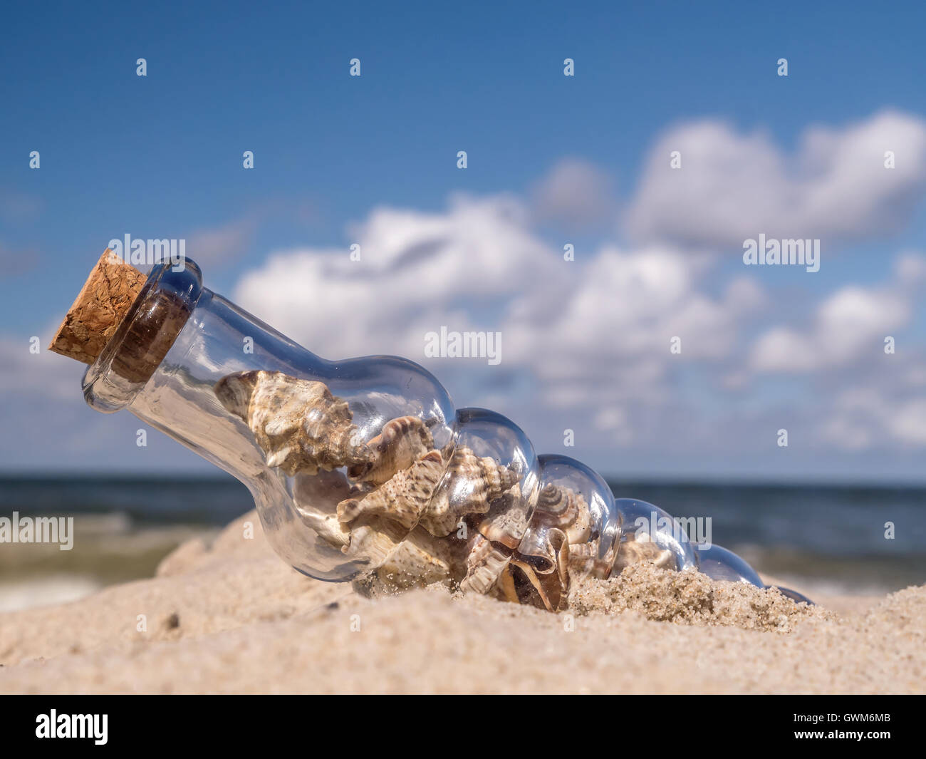 Corked bottle with seashells stuck in the sand on the beach - Stock Image